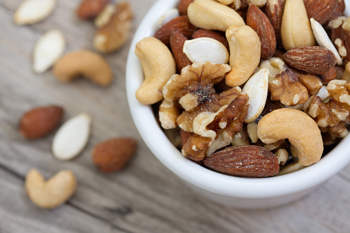 Bowl of mixed nuts on rustic wooden table in natural light._194208