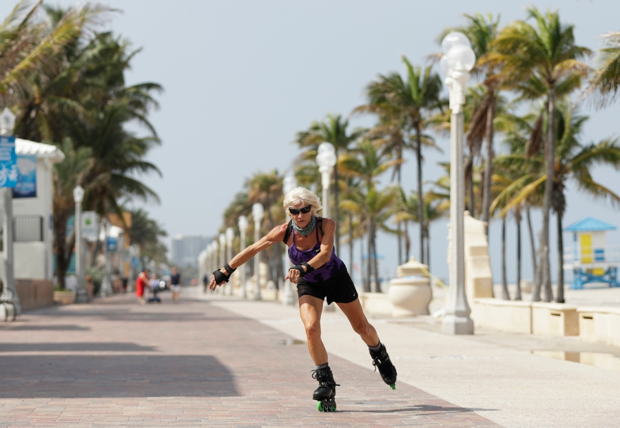 A rollerblader skates on the Hollywood Beach Boardwalk, Tuesday, May 19, 2020, in Hollywood, Fla. Broward County started a phased reopening Monday. (AP Photo/Wilfredo Lee)