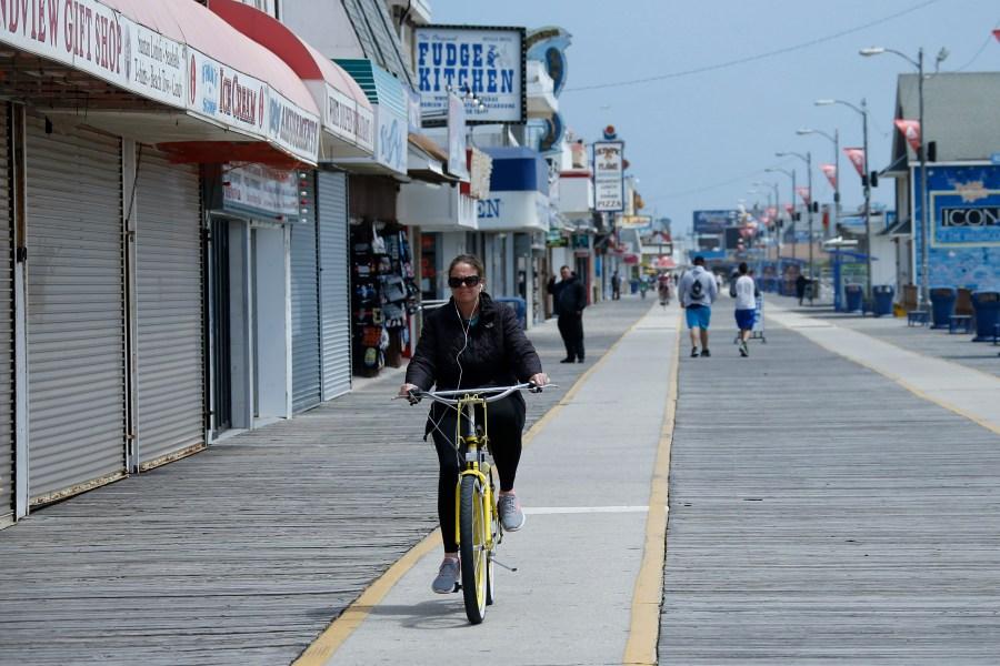 A woman rides a bike down the boardwalk, Thursday, May 21, 2020 in Wildwood, N.J. (AP Photo/Matt Slocum)