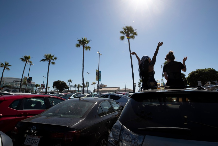 Two women listen to music as they sit through their sunroof in a beach parking lot Thursday, May 21, 2020, in San Diego, CA. (AP Photo/Gregory Bull)