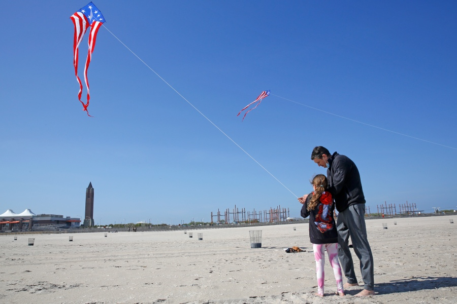 Kaylee Wilmer, 9, of Lindenhurst, N.Y., gets help from her father, Stephen Wilmer, as they fly a kite, Thursday, May 21, 2020, at Jones Beach in Wantagh, N.Y. (AP Photo/Kathy Willens)