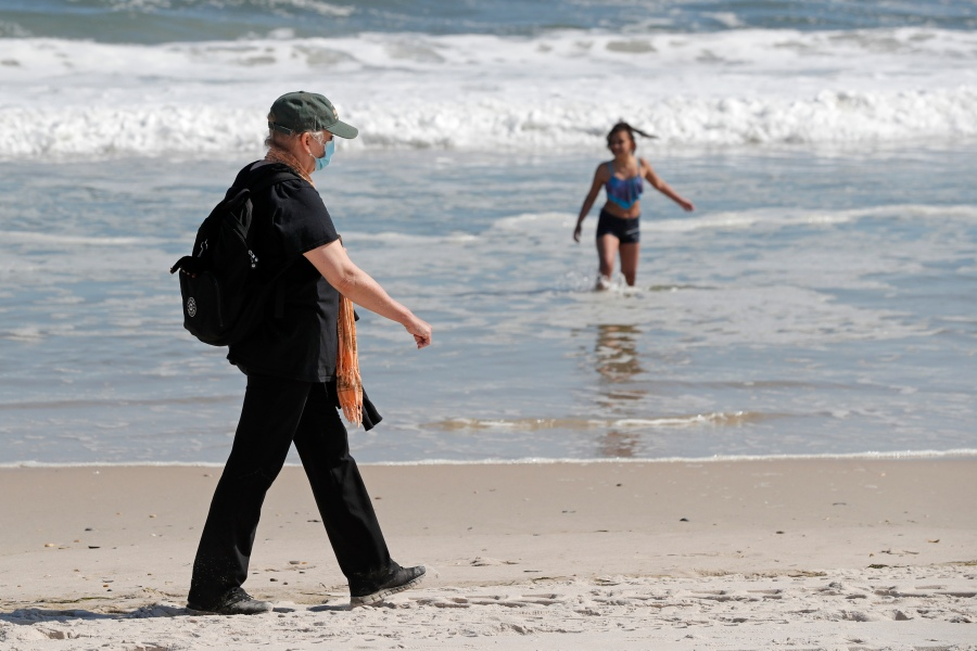 A woman wears a protective face mask during the current coronavirus outbreak, Thursday, May 21, 2020, as she walks on Jones Beach in Wantagh, New York. (AP Photo/Kathy Willens)
