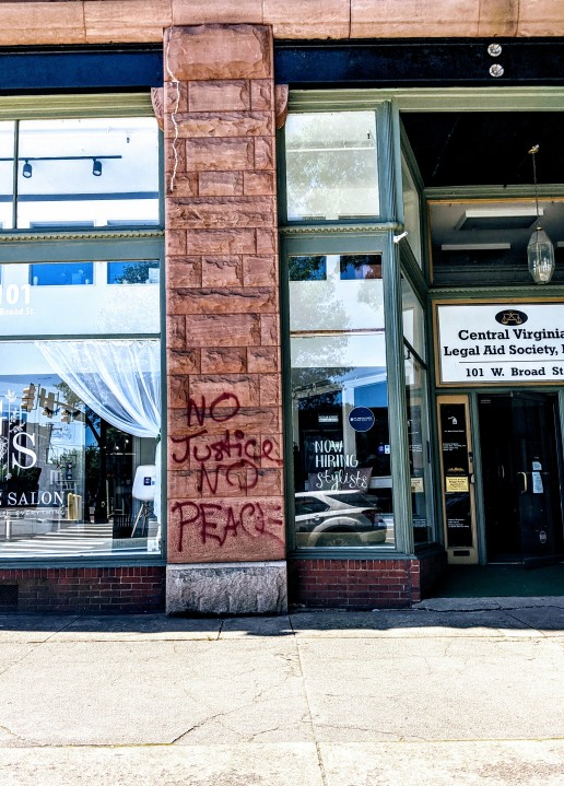 """Graffiti that reads """"No Justice No Peace"""" spray painted on a building in Richmond"""