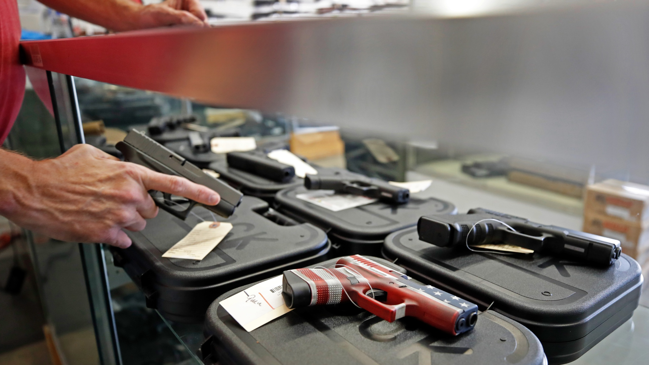 A worker restocks handguns at Davidson Defense in Orem, Utah