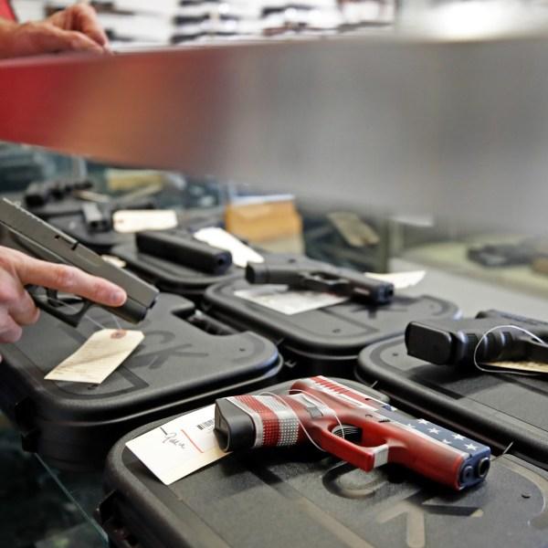 A worker restocks handguns at Davidson Defense in Orem, Utah