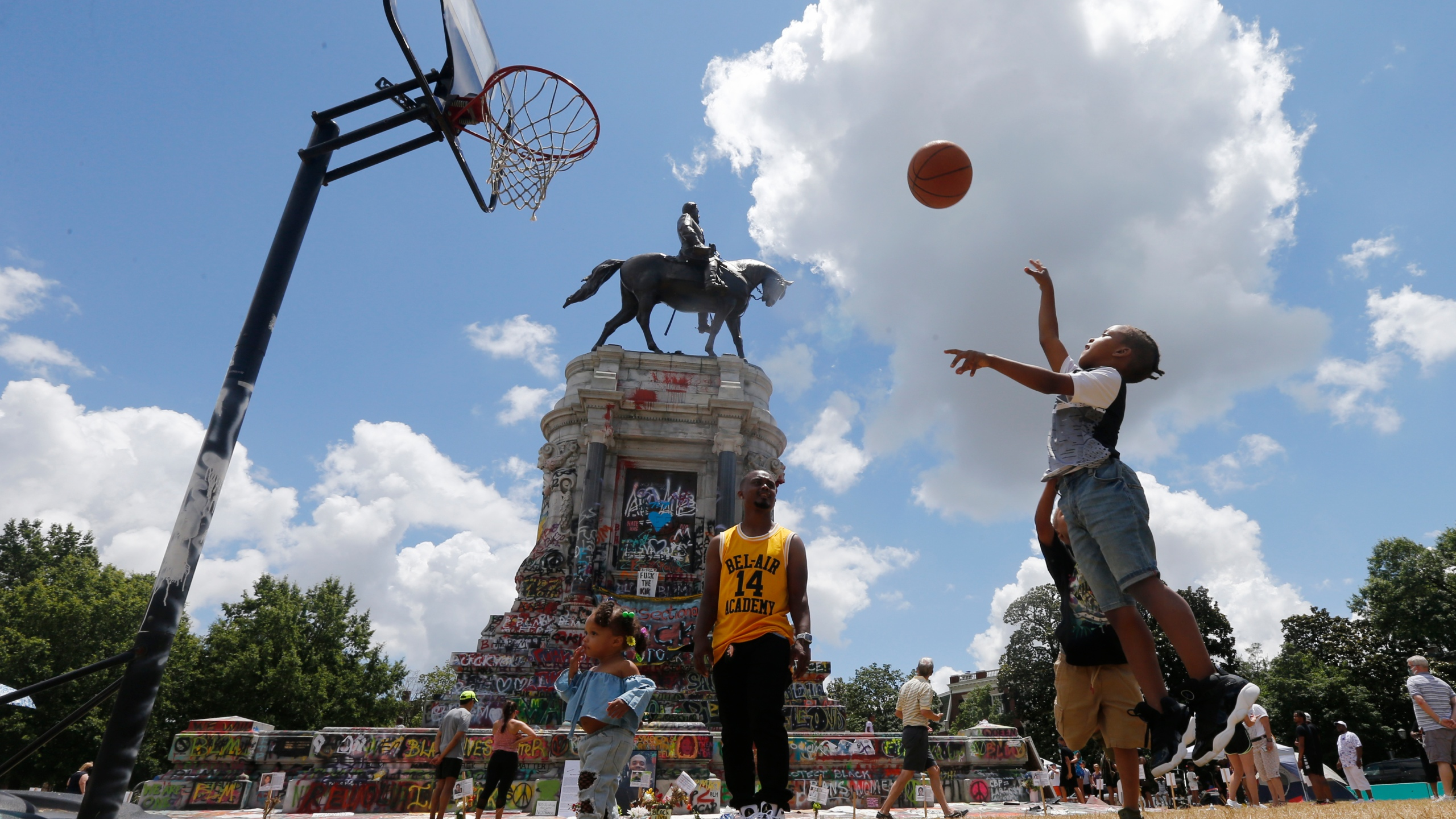 Isaiah Bowen, right, takes a shot as his dad, Garth Bowen, center, looks on at a basketball hoop in front of the statue of Confederate General Robert E. Lee on Monument Avenue
