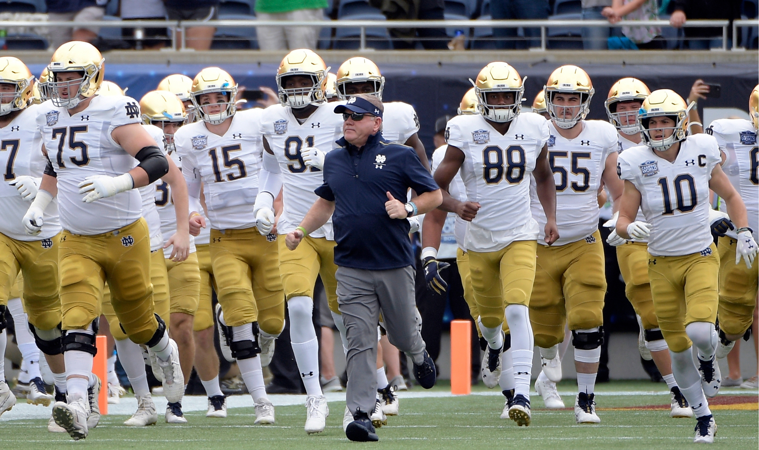 In this Dec. 28, 2019, file photo, Notre Dame head coach Brian Kelly, center, runs onto the field with his players before the Camping World Bowl NCAA college football game against Iowa State in Orlando, Fla.