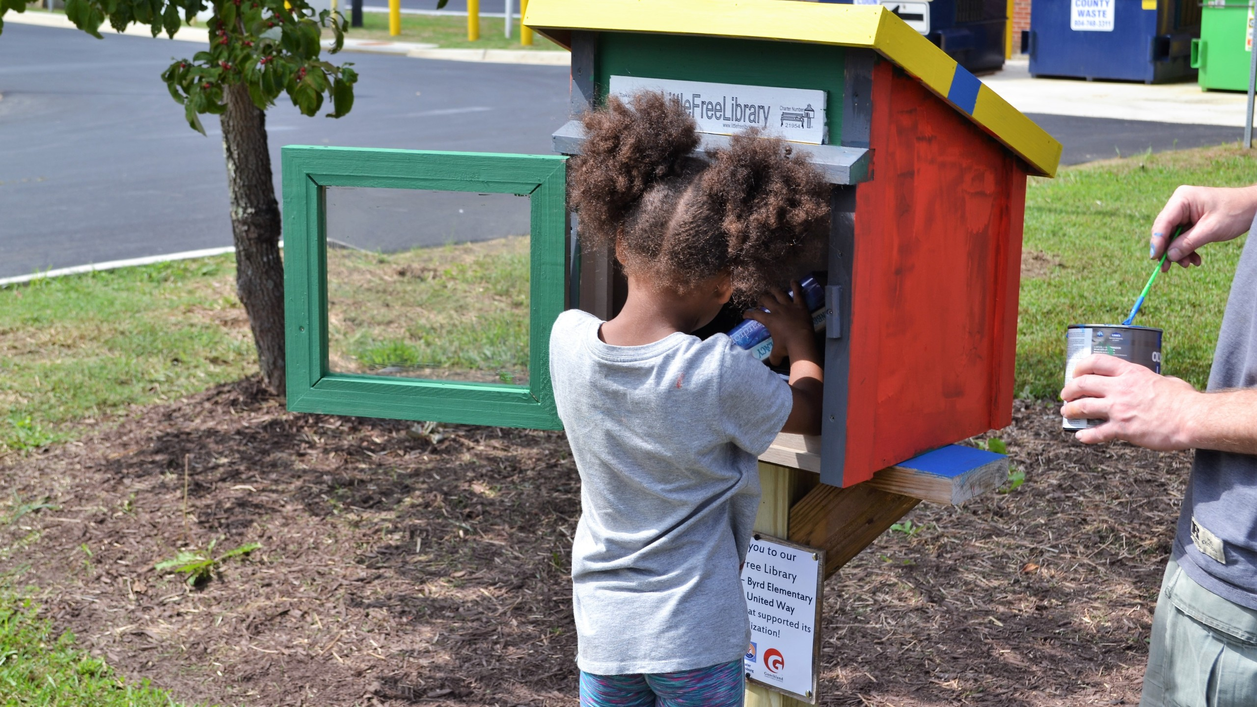 Girl taking a book from a free little library