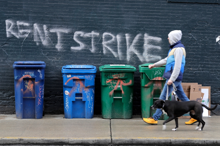 """In this April 1, 2020, photo, a pedestrian walks past graffiti that reads """"Rent Strike"""" in Seattle's Capitol Hill neighborhood."""