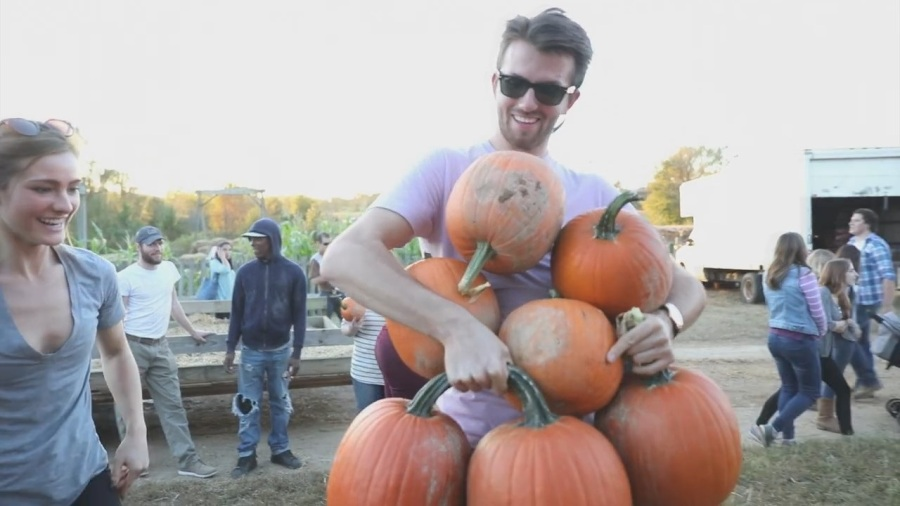 a man juggling pumpkins at a pumpkin patch
