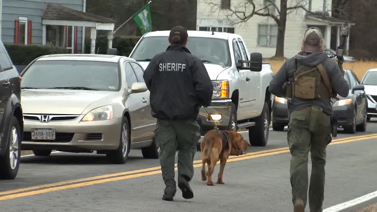 Sheriff's walking with a K9 searching for the driver. (Photos by 8News' Jacob Sexton)