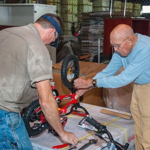 Bud Vye working on bike for kid
