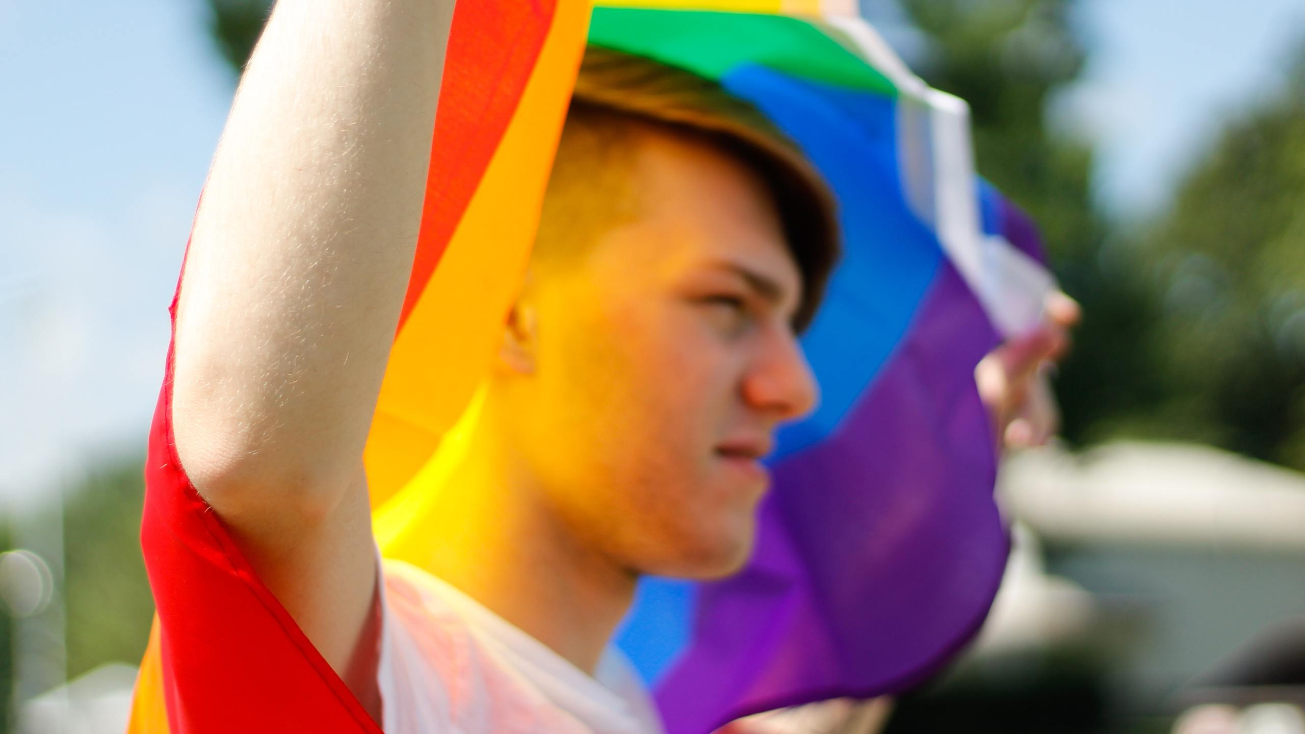 Man holding pride flag (Photo by Brianna Swank from Pexels)