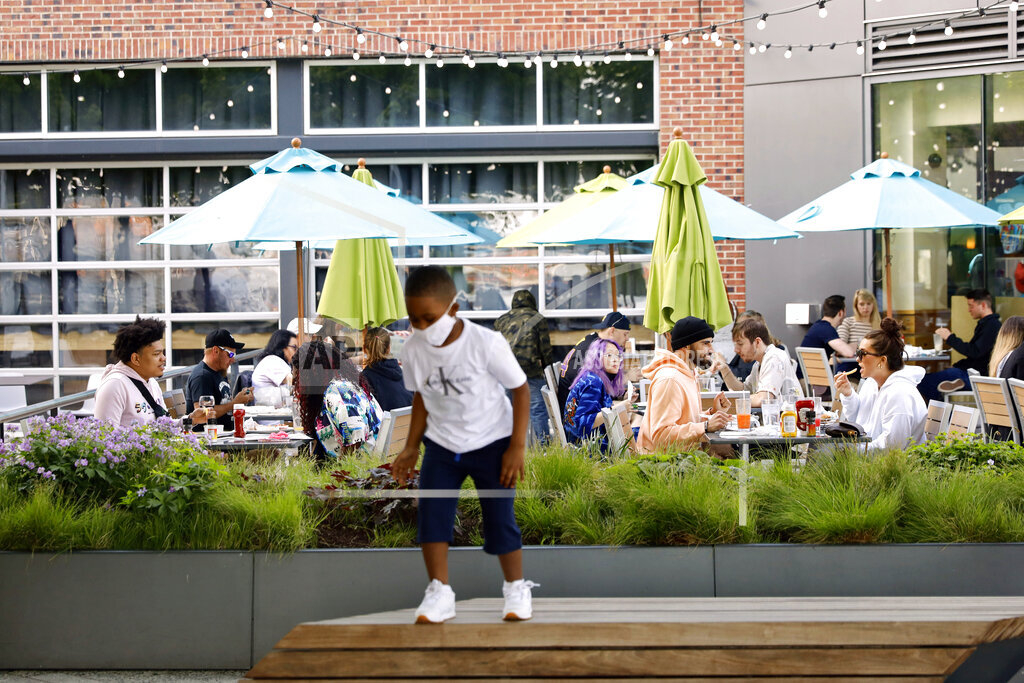 People enjoy their time in an outside sitting area of a restaurant as a child plays in the foreground on Friday, May 14, 2021. The U.S. Centers for Disease Control and Prevention eased its guidelines, saying fully vaccinated people can resume activities without wearing masks. (AP Photo/Shafkat Anowar)